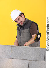 Worker hitting a wall with a sledgehammer