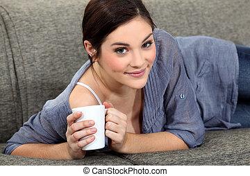Woman laying on sofa with mug of coffee