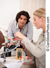 Woman repairing computer and man sitting on a sofa