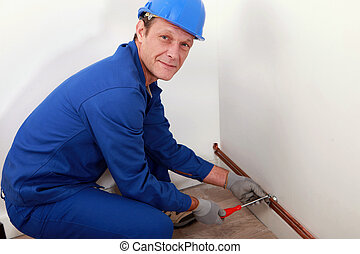 Plumber screwing copper water pipes in place