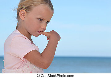Young girl biting her thumbnail
