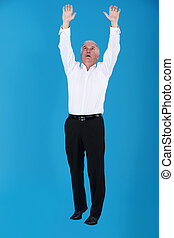 Grey haired businessman reaching into the air