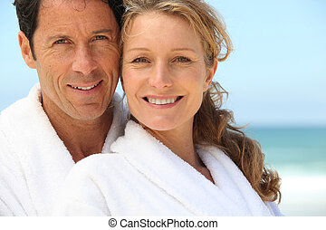 A man and a woman wearing dressing gowns and smiling at us on a beach.