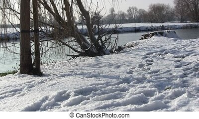 Man walking in the snow by a river.