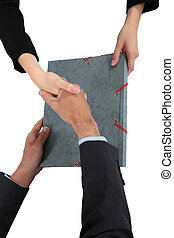 Two businesspeople shaking hands over document