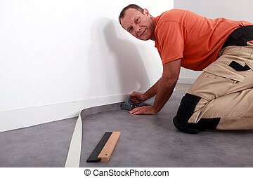 Man cutting carpet