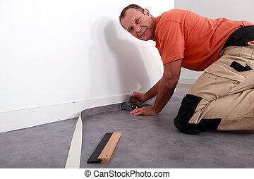 Man cutting carpet