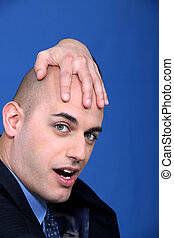 Bald businessman holding his head