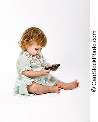 Cute little girl with mobile phone on white background -...