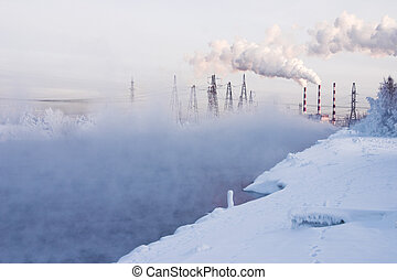 Winter landscape with steam over the river and factory on a...