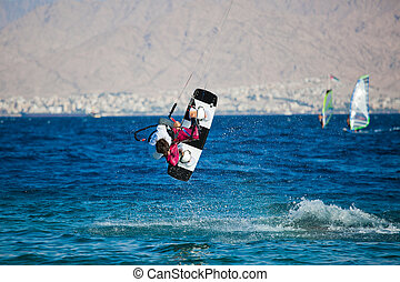 Kite surfing on the sea. The beautiful suntanned young guy...