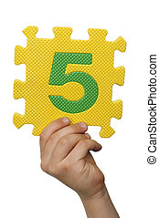 Children hand holding the number Five. White isolated number