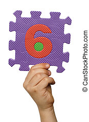 Children hand holding the number Six. White isolated number