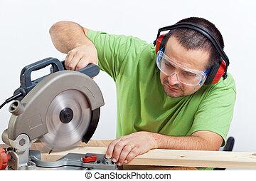 Carpenter cutting wooden plank