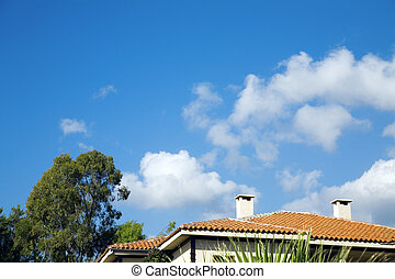 Tree and tile roof of a building against cloudy blue sky