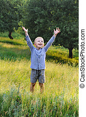 Happy boy - Happy little boy holding hands up in outdoor.Sun...