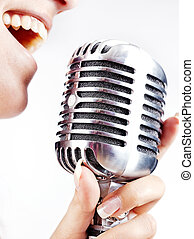 woman singing on retro microphone - woman holding big retro...