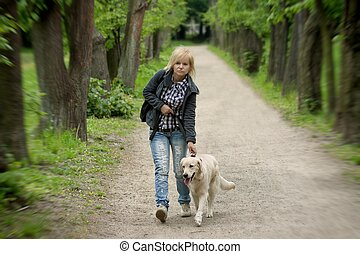 Blond woman walking with her golden retriever dog in the...