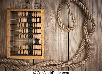 old abacus and rope on a wooden table