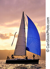 Sail boat against sun with unrecognizable people