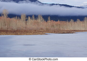 Frozen Lake - Frozen lake with low cloud and view of...
