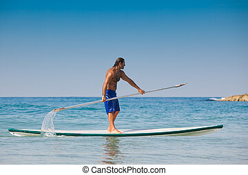 The guy with an oar on a surfboard - The beautiful brawny...
