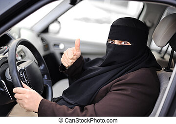 Arabic Muslim woman driving a car with thumb up