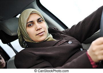 Arabic Muslim woman driving car wearing traditional scarf