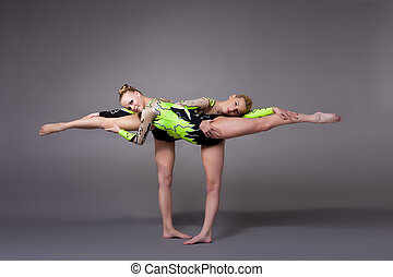 Two young woman as acrobats exercise pair program