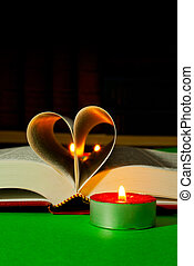 Open book with burning candle - Open book laying on the...