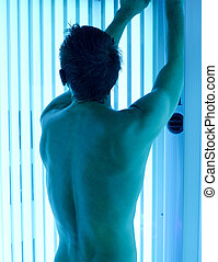 solarium - young man closeup at tanning solarium light on