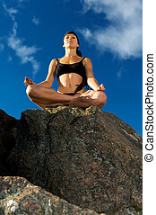 beautiful woman sitting in lotus pose on the beach