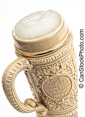 Traditional beer mug with froth over white background