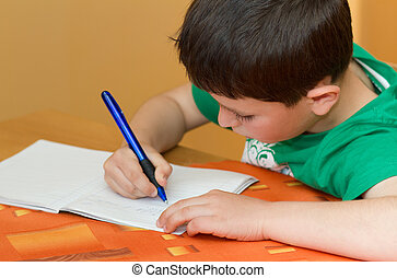 boy writting homework from school in workbook - small school...