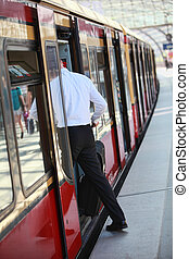 passenger entering the train - Anonymous male passenger with...