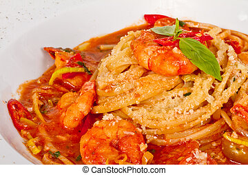 A plate of linguini with sauteed shrimp, tomato, chili and...