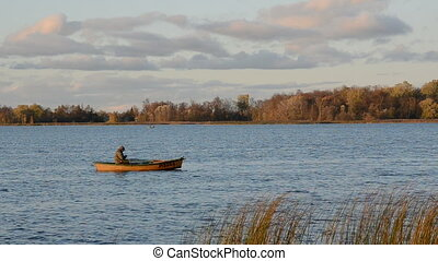 lake and lonely boat with fisherman - autumn lake and lonely...