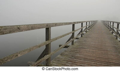 wooden bridge on lake and mist