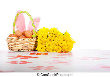 Easter basket with eggs, yellow flowers and bunny ears
