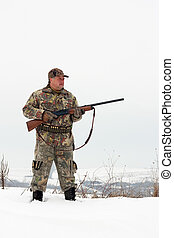 Hunter - Male hunter in camouflage,holding his gun and...