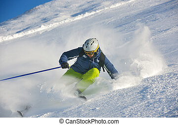 skiing on fresh snow at winter - skier skiing downhill on...