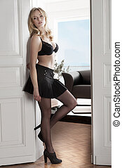 girl in doorway - young sexy blond girl wearing a black bra...