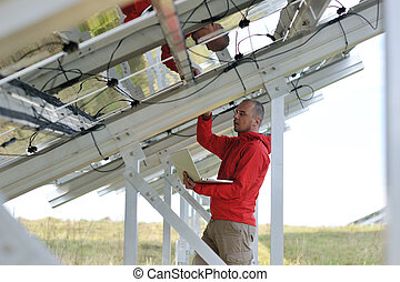 engineer using laptop at solar panels plant field - business...