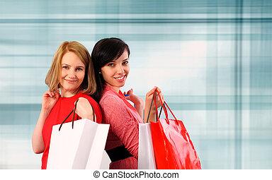 Two young women shopping - Two young women holding shopping...