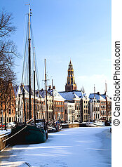 Groningen in snow - view on the channel with ships in...