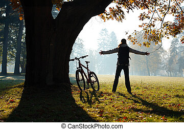 Excited woman cyclist standing in a park with hands...