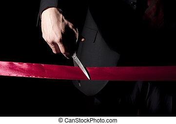 opening of event - man in a suit, cuts a red tape, opening...