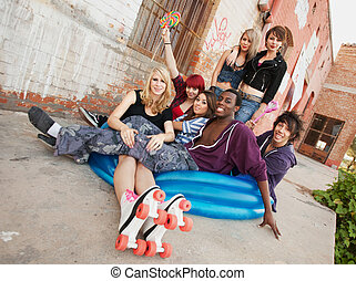 Young and crazy gang of teens sit together behind an abandoned building in a blue inflatable pool.