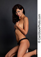 Sexy nude woman isolated in a black background