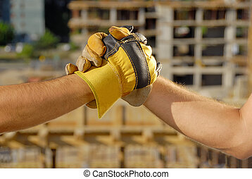Handshake over building site - Two construction technician...